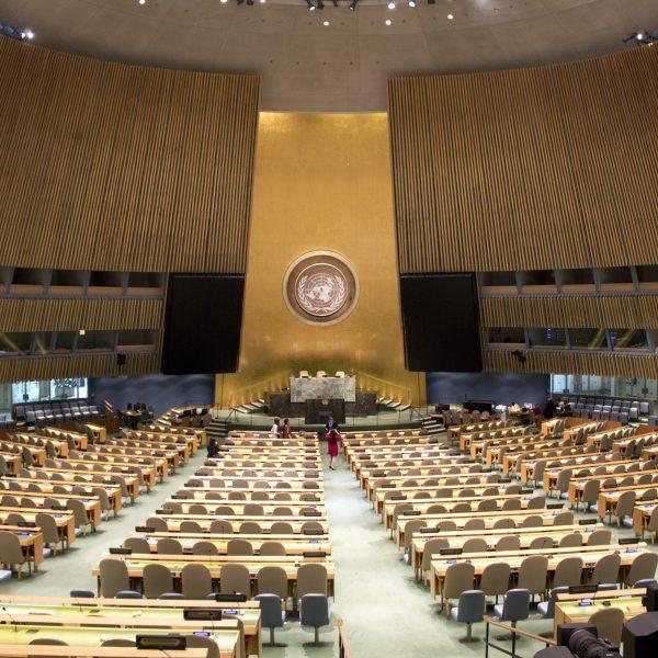 Salle de l'assemblée générale des nations unies dont les sièdes sont tous vides.